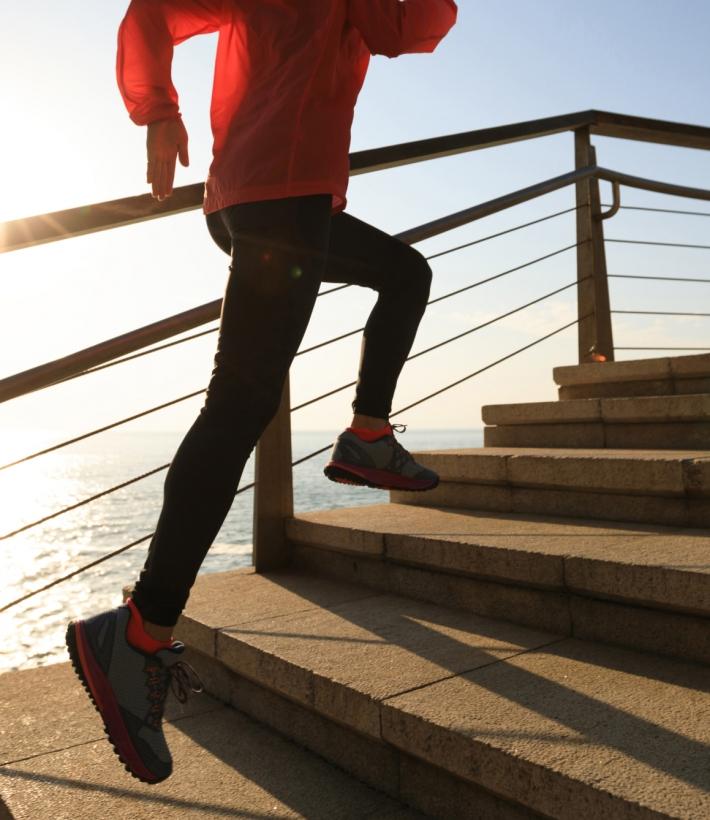 sporty female runner running upstairs on coast trail